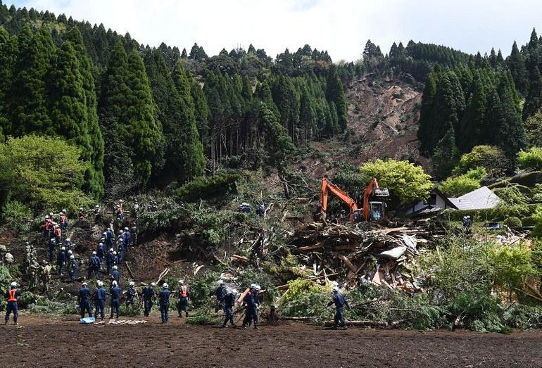 Поиск выживших под оползнем, сошедшем в результате землетрясения в Японии