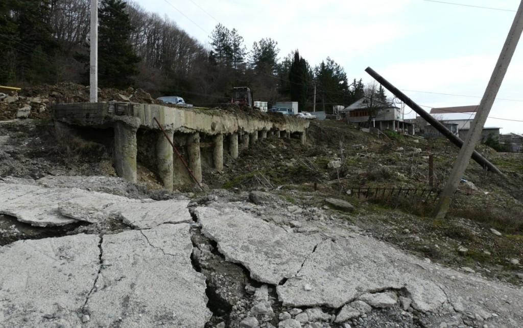 Оползень вязкопластического течения, разрушивший дорогу и нижерасположенные здания, несмотря на защитную стенку из куста буронабивных свай, в которой отсутствуют следы разрушений. Грунты оползня обтекали сваи